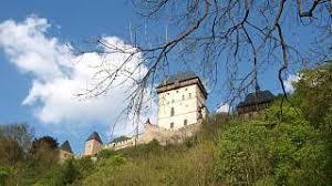 """Oblíbené české hrady Karlštejn a Křivoklát navštívil snad každý Čech, ať už ve školním věku, nebo později se svou rodinou či přáteli. Při vzpomínce na prohlídku se nám vybaví leccos ze života jejich zakladatelů nebo z pohnuté historie. Jsou však jevy a události, o kterých se nezmiňují průvodci obklopení houfem turistů ani tištěné bedekry. Vydejme se za nimi do časů dávných, ale i nedávno minulých. Kateřinský zvon a záhadná studna """"Život Karlův schyloval se k jeseni. Jedné noci listopadové zazněly z věží karlštejnských temné zvučné rázy zvonů. A zvonění neustávalo, mohutníc v jímavé kvílení. Zvoník karlštejnský, jenž držel právě v rukou klíče, strnul v úžasu a zůstal stát bez hlesu jako sloup. V domnění, že si tu zahrála náhoda nebo zlomyslnost, spěchal chvatně nahoru ke zvonici. Leč vystoupiv nahoru, uzřel jen zvony a jejich kovová srdce, houpající se smutečně odměřenými rázy. Byly to hrany Karlovy."""" Tolik dobový kronikář. Podle pověsti se to stalo 29. listopadu 1378. Skutečně však v ten den zemřel zakladatel Karlštejna, císař římský a král český Karel IV., známý jako Otec vlasti. Je to neobvyklý zážitek stát pod kateřinským zvonem – patronkou Karla IV. i celého Karlštejna totiž byla svatá Kateřina – a v pravém poledni poslouchat jeho zvuk. Otevřenými okny hodinové věže nad druhou bránou je zvuk slyšet nejméně na vzdálenost pěti kilometrů. """"Ulit jsem byl za Karla IV. v roce 1372, přelit jsem byl za vlády Rudolfa II. v roce 1609,"""" je psáno na zvonu. Jedním z nejnavštěvovanějších hradních míst je pověstná karlštejnská studna. Spustit se do ní v okovu nelze; jednak je šachta zabezpečená mříží, jednak je ve studni, hluboké 78 metrů, dvacetimetrový sloupec vody. Ví se však toho o ní dost. Budovala se samozřejmě hned na počátku výstavby hradu. Je to vlastně cisterna – napájela se jednou až dvakrát do roka vodou z potoka; tento úkon prováděl výhradně purkrabí. Studnu hloubili pověstní kutnohorští havíři, zatímco k vybudování tajné štoly, sloužící jako východ pro zvědy nebo"""